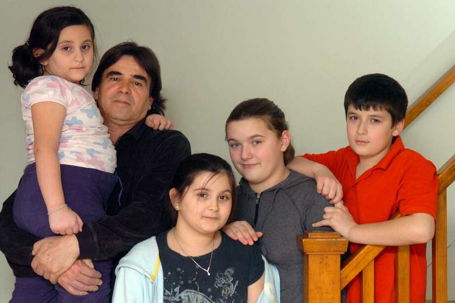 Skender Emini poses with his three nieces (from left), Afertita, Dorisa and Dorentina, and nephew Dorart, in their Naugatuck, Conn. home Feb. 4th, 2010. Emini, a citizen of Serbia, has cared for the four children, who are American citizens, since the murder of their parents in January of 2007. Photo: Autumn Driscoll / Connecticut Post