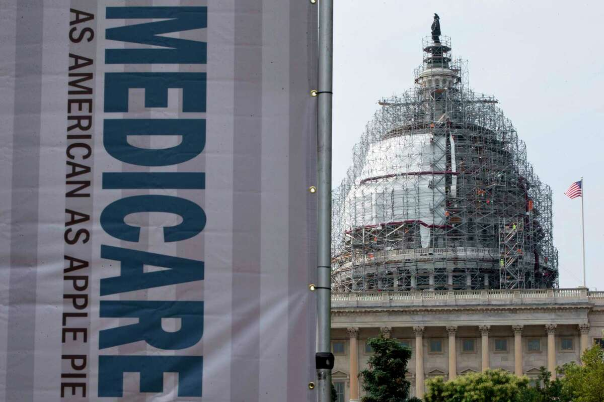 FILE - In this July 30, 2015 file photo, a sign supporting Medicare is seen on Capitol Hill in Washington. A government report says Medicare beneficiaries can end up with higher hospital bills for some medical services as outpatients than as inpatients. In the topsy-turvy world of Medicare billing, you may pay more for outpatient care. (AP Photo/Jacquelyn Martin, File)