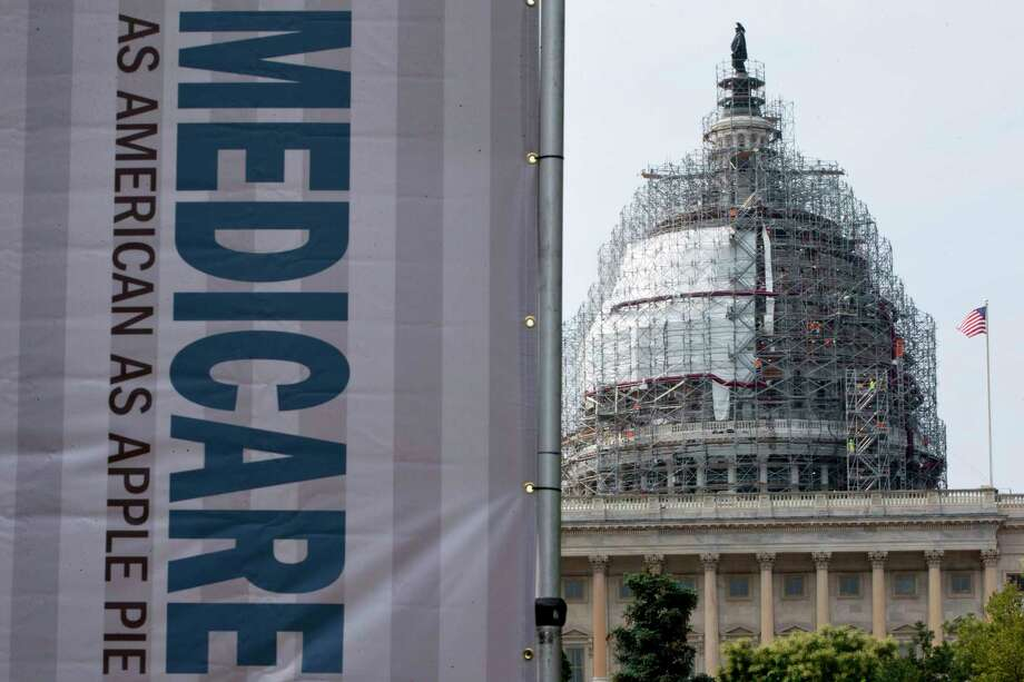 FILE - In this July 30, 2015 file photo, a sign supporting Medicare is seen on Capitol Hill in Washington. A government report says Medicare beneficiaries can end up with higher hospital bills for some medical services as outpatients than as inpatients. In the topsy-turvy world of Medicare billing, you may pay more for outpatient care. (AP Photo/Jacquelyn Martin, File) Photo: Jacquelyn Martin, STF / Copyright 2016 The Associated Press. All rights reserved. This material may not be published, broadcast, rewritten or redistribu