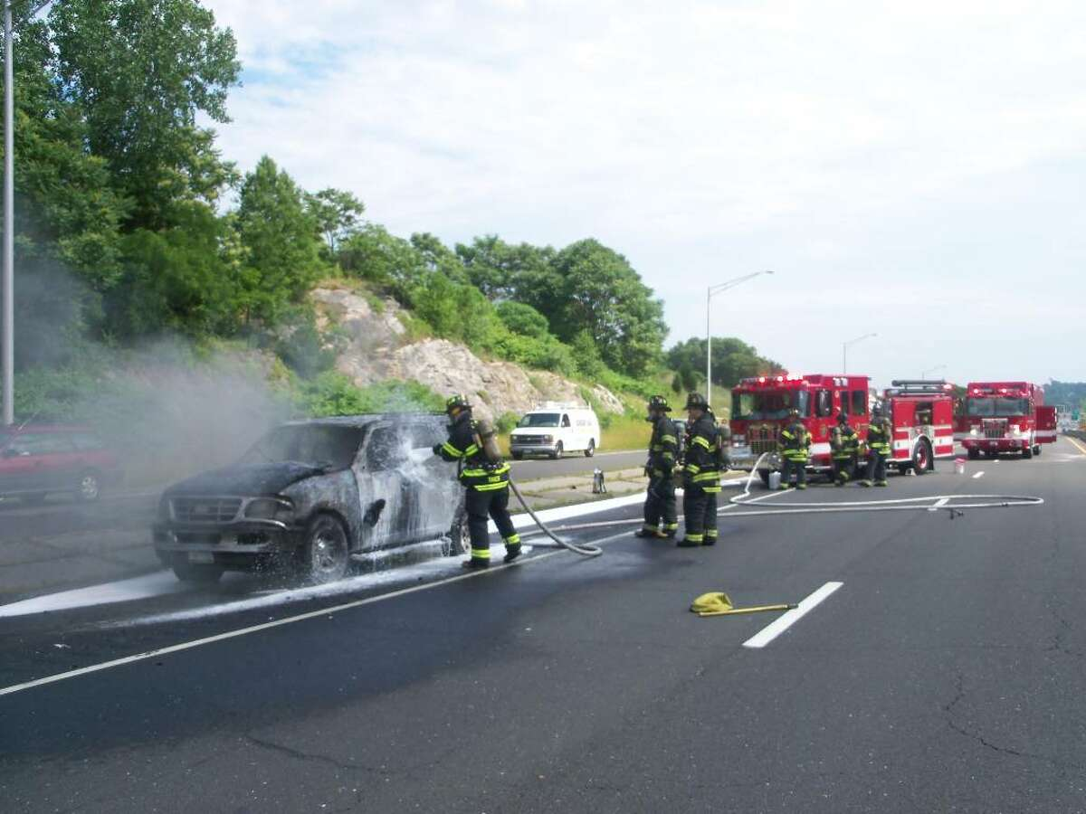 Norwalk firefighters extinguish a car fire on the Route 7 connector Thursday afternoon. The driver of the car escaped uninjured.