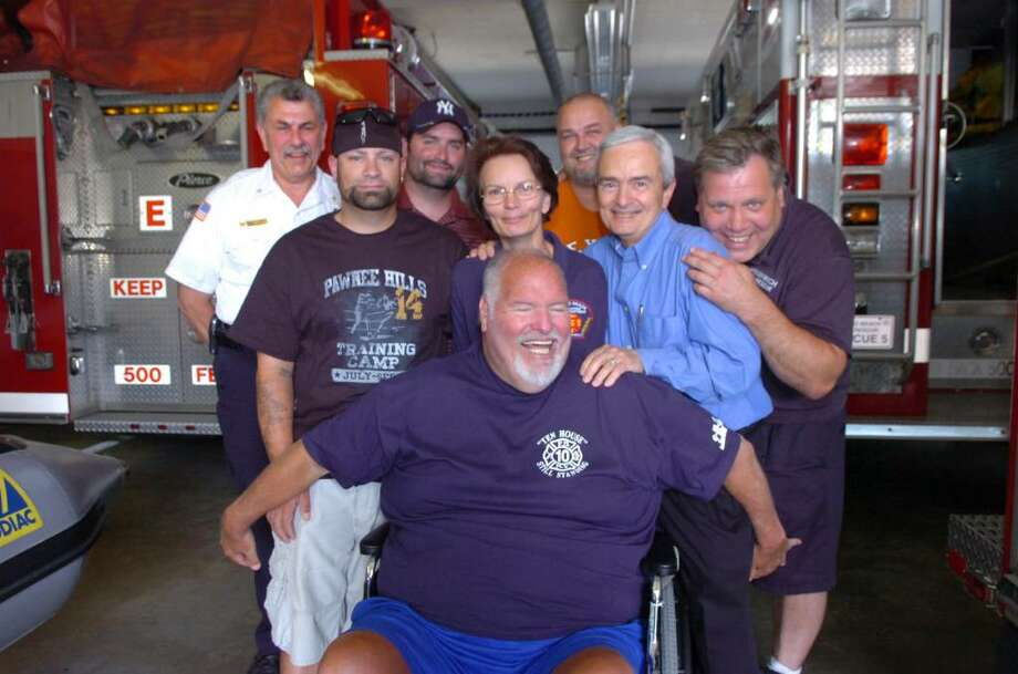 Kevin Perna, center, gives his friends a group hug at the Sound Beach Volunteer Fire Department, on Thursday, June 10, 2010.  The Greenwich volunteer has been diagnosed with a disorder that confined him to a wheelchair, so volunteers have organized a benefit to help raise money for a handicapped assessible van.  Second row, from left: Chris Perna, his son, Cathy Perna, his wife, Terry Paton, Terry Murphy.  Third row, from left: Shawn McDonnell, Sean Perna, his son, Wayne Jordan. Photo: Helen Neafsey / Greenwich Time