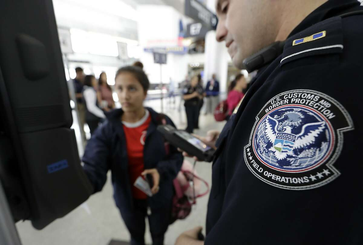 A U.S. Customs and Border Protection officer helps a passenger navigate one of the new facial recognition kiosks at an airport gate.