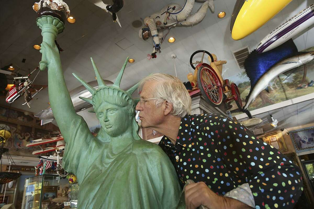 Owner Jamis MacNiven kisses the small-scale Statue of Liberty at Buck's, just one of the many tchotchkes that fill the restaurant near Sand Hill Road.
