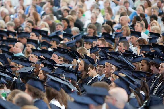 Graduates listen to Principal Mark Murrell during Wednesday's commencement ceremonies for The Woodlands College Park High School at the Cynthia Woods Mitchell Pavilion.