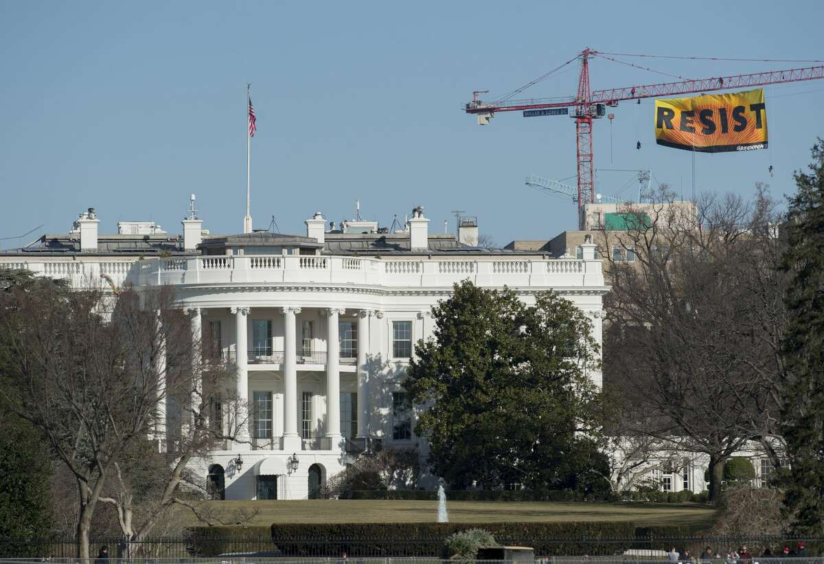 (FILES) Greenpeace protesters unfold a banner reading