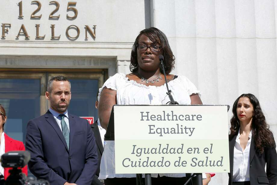Healthcare worker and Medi-Cal patient Crystal Pryor (middle) talks about her insurance dilemmas in front of the René C. Davidson Courthouse on Tuesday in Oakland. Photo: Liz Hafalia, The Chronicle