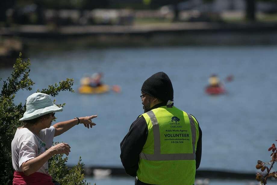 Laura Goderez informs Emmanuel Entes, Lake Supervisor, of a trash can in Lake Merritt on Thursday, June 29, 2017 in Oakland , CA. Photo: Paul Kuroda, Special To The Chronicle