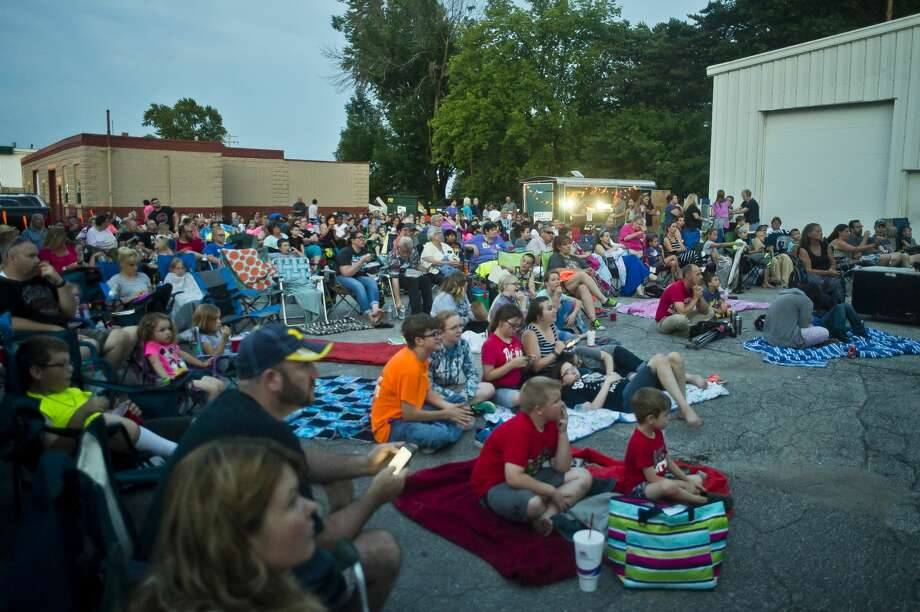 People gather to watch Boss Baby projected onto a wall outside of Tri-City Furniture during Movies Under the Moonlight on Tuesday, July 11, 2017 in Auburn. Photo: (Katy Kildee/kkildee@mdn.net)