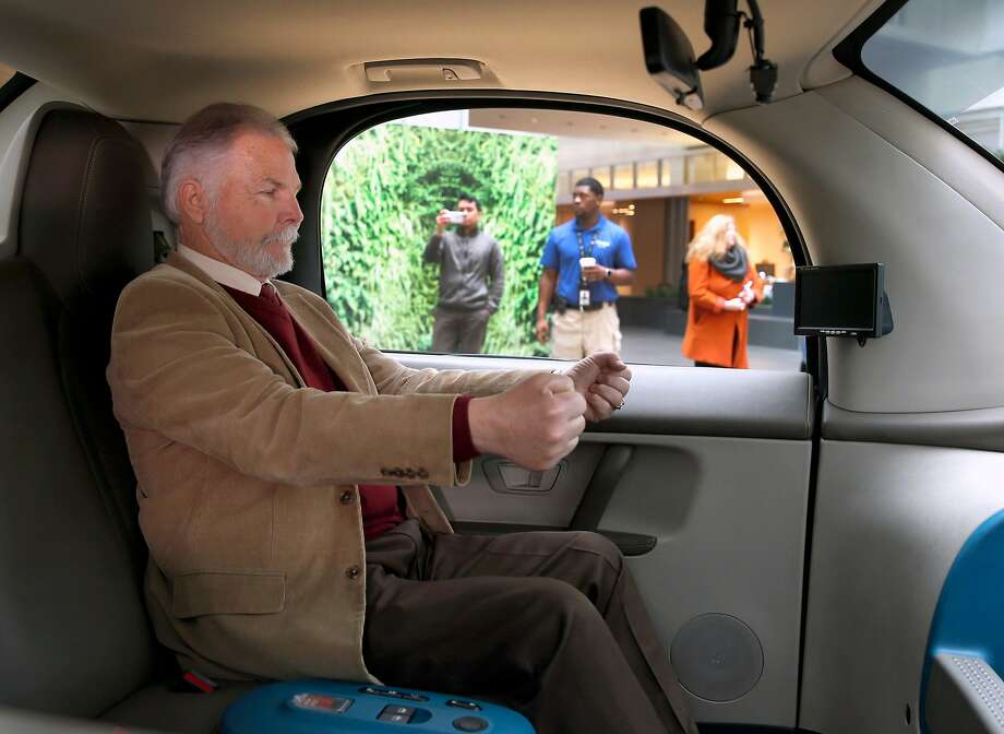 Steve Mahan, who is blind, pretends to take the wheel of a Waymo driverless car unveiled in December. Photo: Paul Chinn, The Chronicle