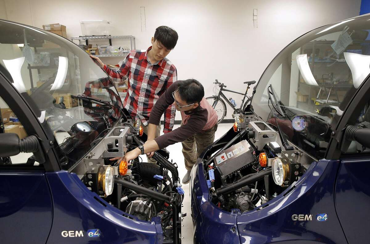 David Wong, Robotics Hardware Engineer, right, and Di Meng, engineering intern, left, look over the front of the Polaris Gem E4 for improvements in design for their third vehicle �that will be converted to autonomous driving at Auro Robotics in Santa Clara, Calif., on Thursday, March 2, 2017.