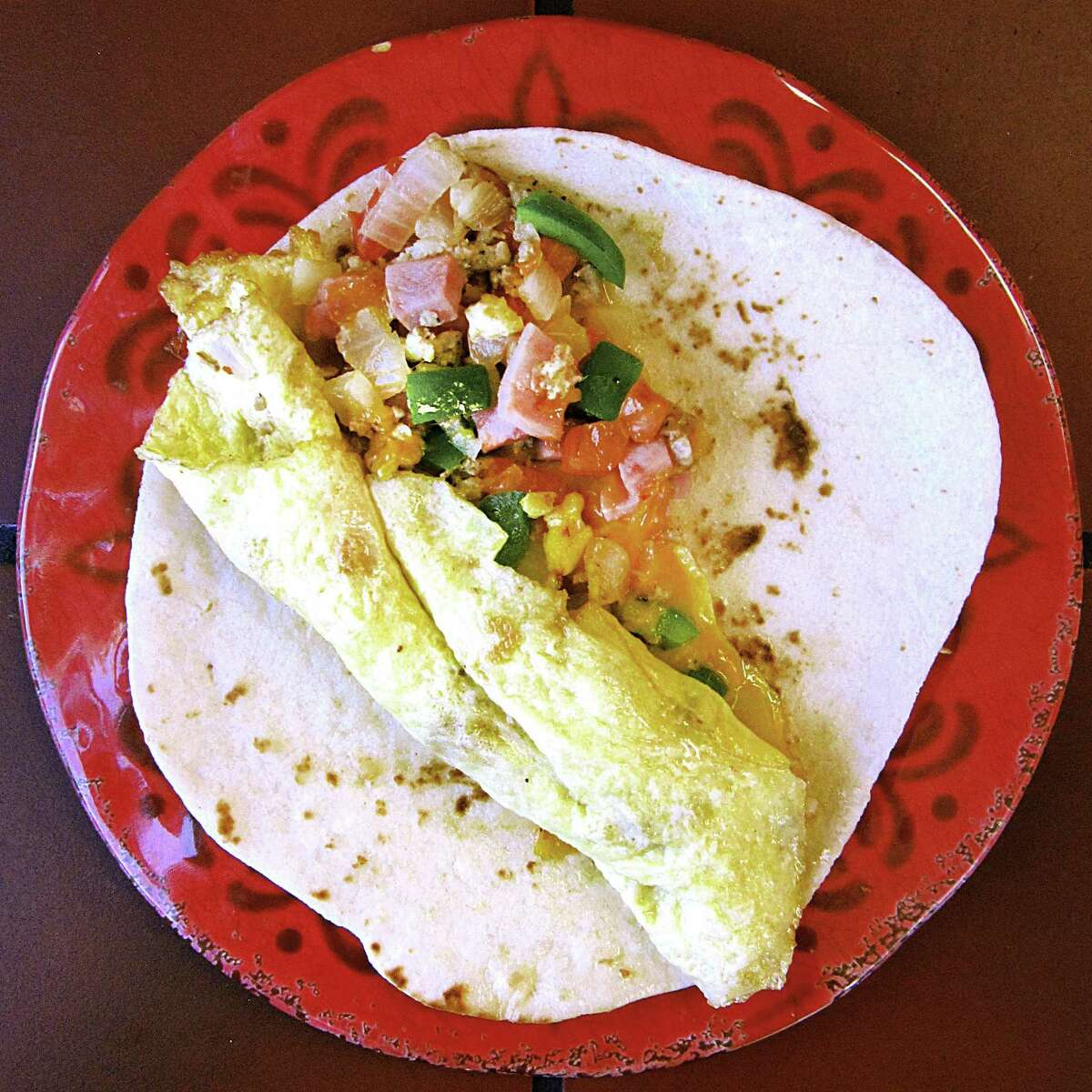 Omelet breakfast taco with eggs, ham, sausage, peppers, onions, tomatoes and cheese on a handmade flour tortilla from Ruthie's Mexican Restaurant.