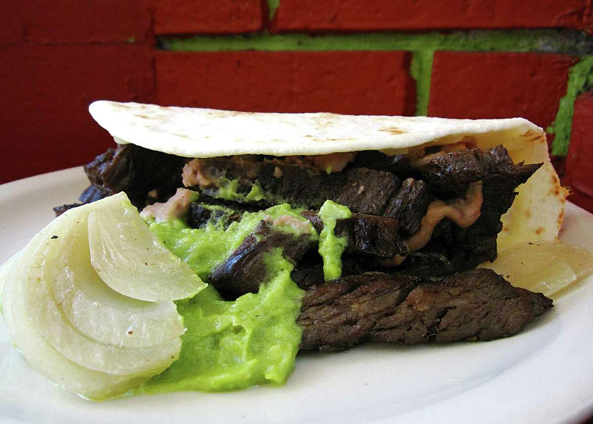 Mini-Norteño taco with beef fajitas, cheese, beans, guacamole and grilled onions on a toasted handmade flour tortilla from Ruthie's Mexican Restaurant.