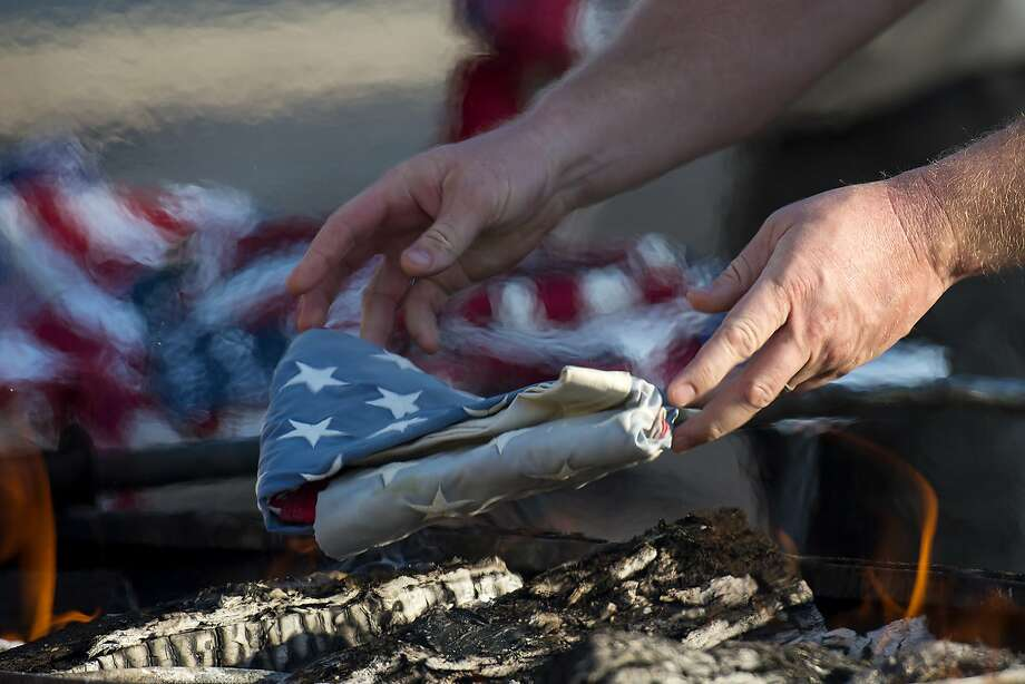 A person drops an American flag into the fire during a flag retirement ceremony in Lindale, Texas. Photo: Chelsea Purgahn, Associated Press
