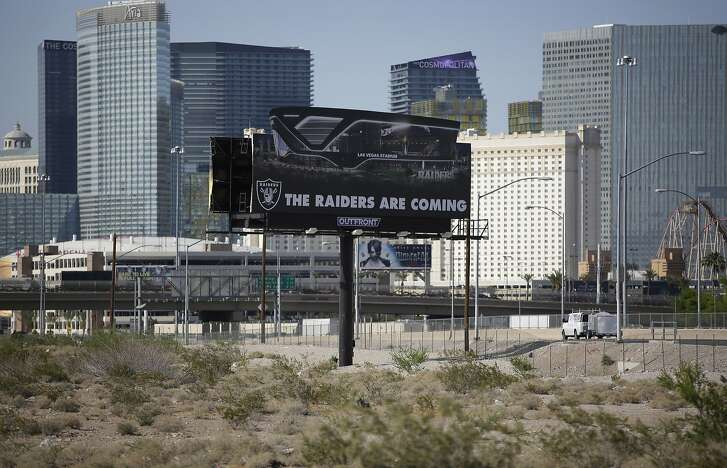 FILE - In this May 11, 2017, file photo, a sign advertises the Raiders football team near a site for the team's proposed stadium in Las Vegas. Days after the Nevada Legislature approved a tax increase to help pay for an NFL stadium, lawmakers touted several provisions in the bill that they said would ensure that southern Nevada residents are directly benefited from the construction of the 65,000-seat facility. Eight months later, however, it's still unclear how the Oakland Raiders and the public board overseeing the $1.9 billion project will follow through with the promises. (AP Photo/John Locher, File)