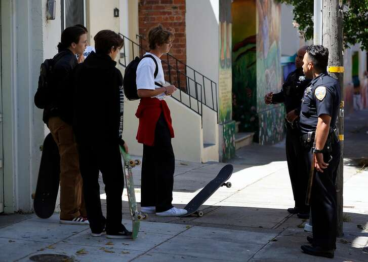 San Francisco police officers talk to a group of kids about riding their skateboards down 18th St. in the Mission neighborhood in San Francisco , Ca., on Wednesday July 12, 2017.