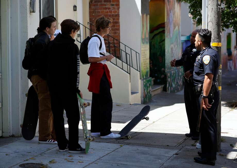 San Francisco police officers talk to a group of kids about riding their skateboards down 18th St. in the Mission neighborhood in San Francisco , Ca., on Wednesday July 12, 2017. Photo: Michael Macor, The Chronicle