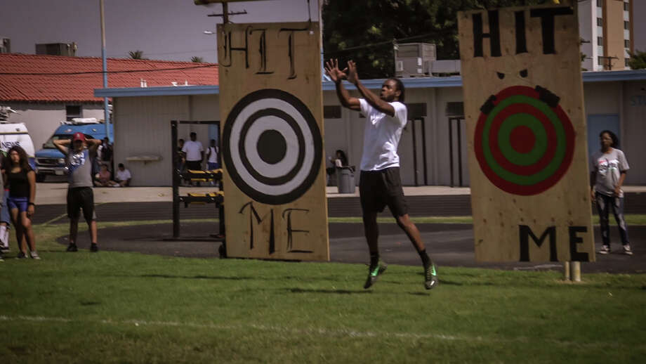"""Seahawks cornerback Richard Sherman, in partnership with """"The Jerky Challenge"""" presented by Oberto Beef Jerky, competed against a football-throwing robot during an event at Compton High School on Tuesday. Photo: COURTESY CHRIS CORBIN"""