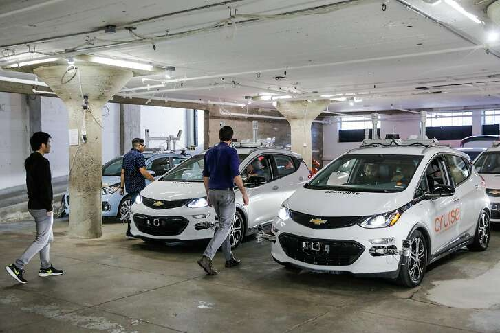 Autonomous vehicle trainer Alex Kexel (right) and operations team lead Roy Ysmael (second from left) prepare cars for test drives at Cruise Automation, an autonomous driving car company in the SOMA district of San Francisco, California, on Tuesday, March 14, 2017.