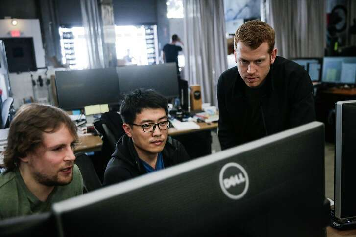 (l-r) Gautier Minster and Wei Mou chat with CEO Kyle Vogt while working at Cruise Automation, an autonomous driving car company in the SOMA district of San Francisco, California, on Tuesday, March 14, 2017.