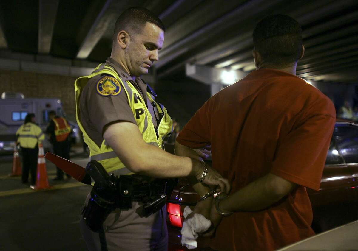MIAMI - DECEMBER 15: Trooper David Casillas, from the Florida Highway Patrol, arrests a driver for driving under the influence after a field sobriety test at a DUI checkpoint December 15, 2006 in Miami, Florida. The city of Miami, with the help of other police departments, will be conducting saturation patrols and setting up checkpoints during the holiday period looking to apprehend drivers for impaired driving and other traffic violations. (Photo by Joe Raedle/Getty Images)