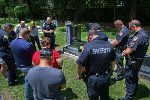 Harris County Sheriff's Office chaplain Lt. Donald Savelle leads a prayer next to the new memorial to Harris County Sheriff's Deputy Darren Goforth at Woodlawn Cemetery, Wednesday, July 12, 2017. Goforth, 47, was gunned down on the evening of Aug. 28, 2015, as he pumped gas into his Harris County Sheriff's Department patrol vehicle at a northwest Harris County gas station.