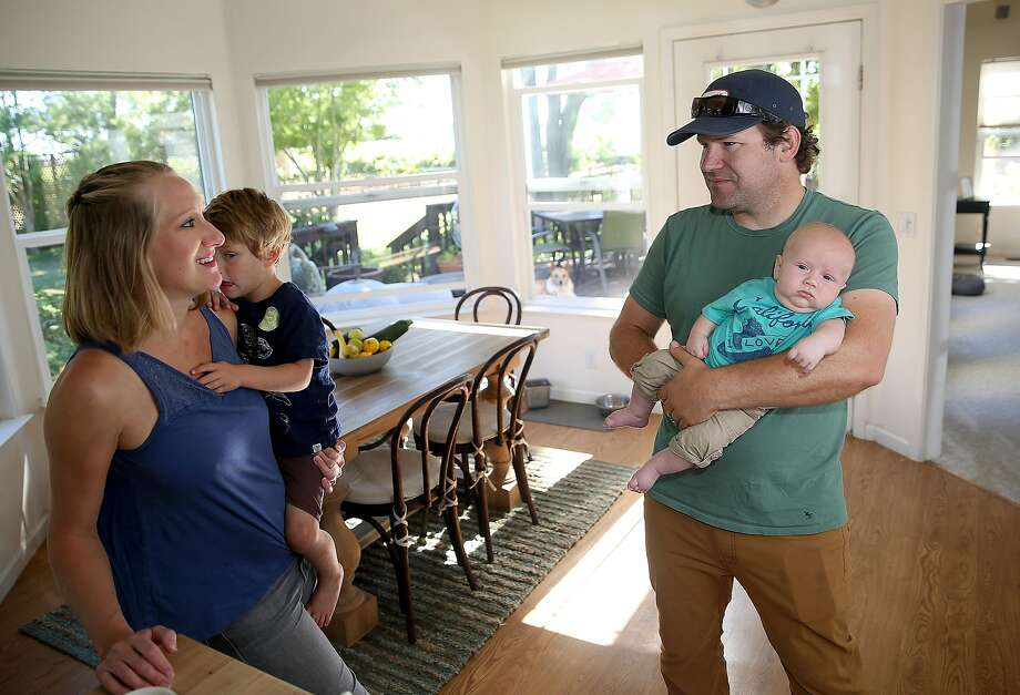 Shauna Des Voignes holds 2-year-old Henry and Jake Des Voignes holds 2-month-old Leo at their home on their 20-acre farm and vineyard in Acampo (San Joaquin County). Photo: Liz Hafalia, The Chronicle
