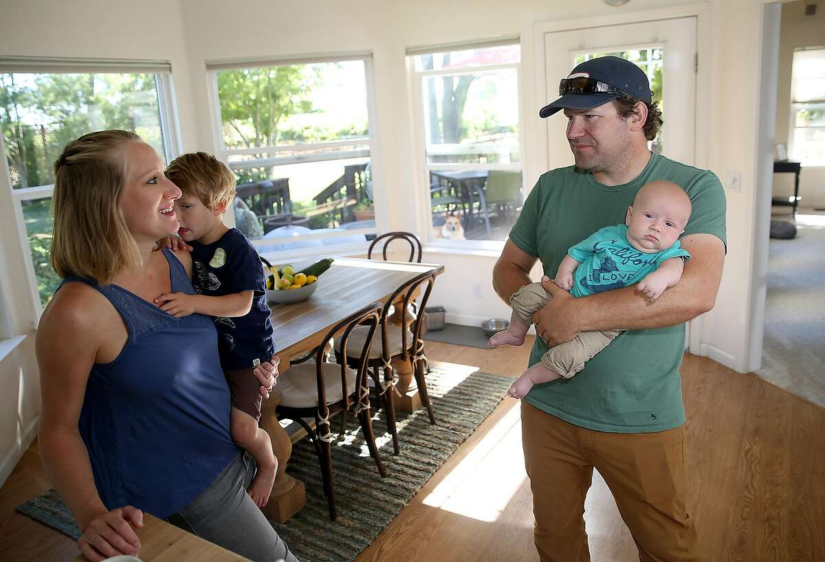 Bay area chefs Shauna Des Voignes (left) holds their two year old Henry Des Voignes and Jake Des Voignes (right) holds their 2 month old Leo De Voignes at home on their 20 acre farm and vineyard of orange musket on Monday, June 26, 2017, in Acampo, Calif.