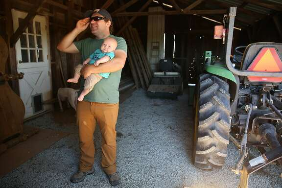 Bay area chef Jake Des Voignes holds his two month old son while he shows the tools and tractor in the barn on their 20 acre farm and vineyard of orange musket on Monday, June 26, 2017, in Acampo, Calif.