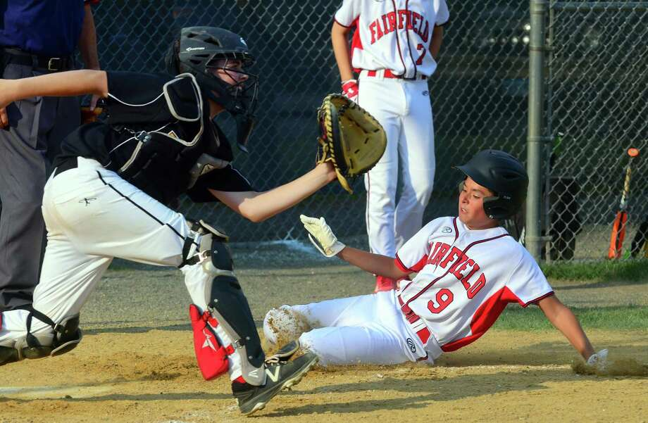 Fairfield American's Sean O'Neil beats the tag at home plate against Trumbull American on Wednesday night at Unity Park. Waiting for the ball is Trumbull catcher Jack Arcamone. Photo: Christian Abraham / Hearst Connecticut Media / Connecticut Post