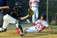 Fairfield American's Sean O'Neil beats the tag at home plate against Trumbull American on Wednesday night at Unity Park. Waiting for the ball is Trumbull catcher Jack Arcamone.