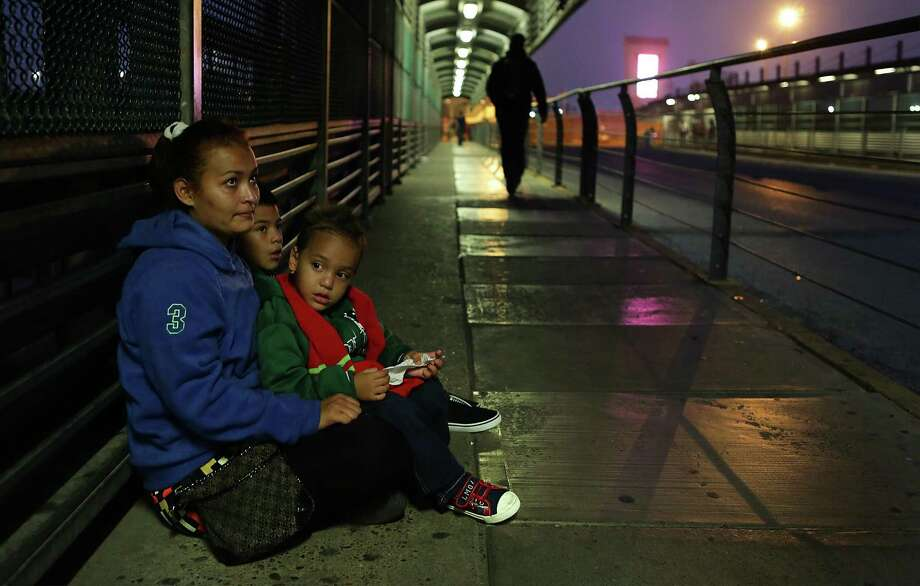 Alejandra Flores, from Honduras, huddles with her sons Alexande Josue Romero, 3, and Brision Josue Romero, 10, on the Hidalgo International Bridge in the early hours on Tuesday, Dec. 27, 2016, hoping to be let in the U.S. after a 22 day journey from their home in Honduras, spending Christmas on the road. Photo: Bob Owen, Staff / San Antonio Express-News / ©2016 San Antonio Express-News