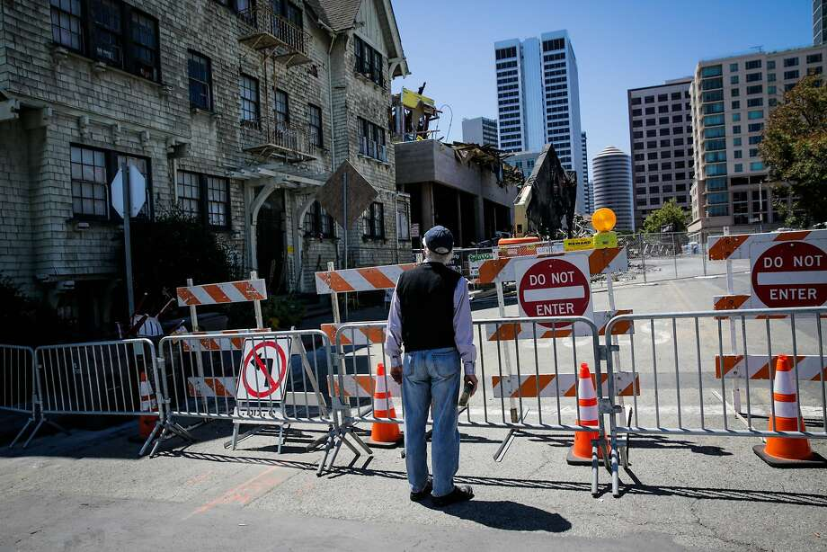 A man stops to look at the scene of a fire that tore through a seven-story housing and retail project under construction in Oakland. Photo: Gabrielle Lurie, The Chronicle