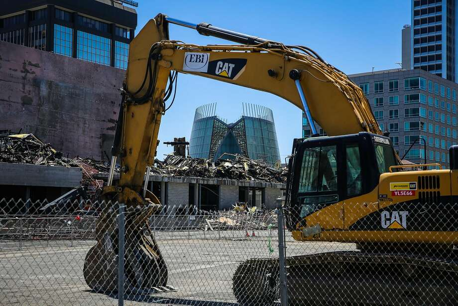 Heavy construction equipment is next to the scene of a fire that tore through a seven-story housing and retail project under construction in Oakland. Photo: Gabrielle Lurie, The Chronicle