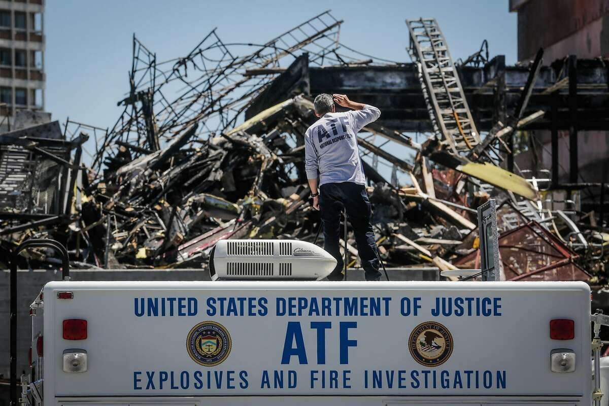 ATF special agent Ken Whiteley surveys the scene of a fire that tore through a seven-story housing and retail project under construction last Friday in Oakland, California, on Monday, July 10, 2017.v