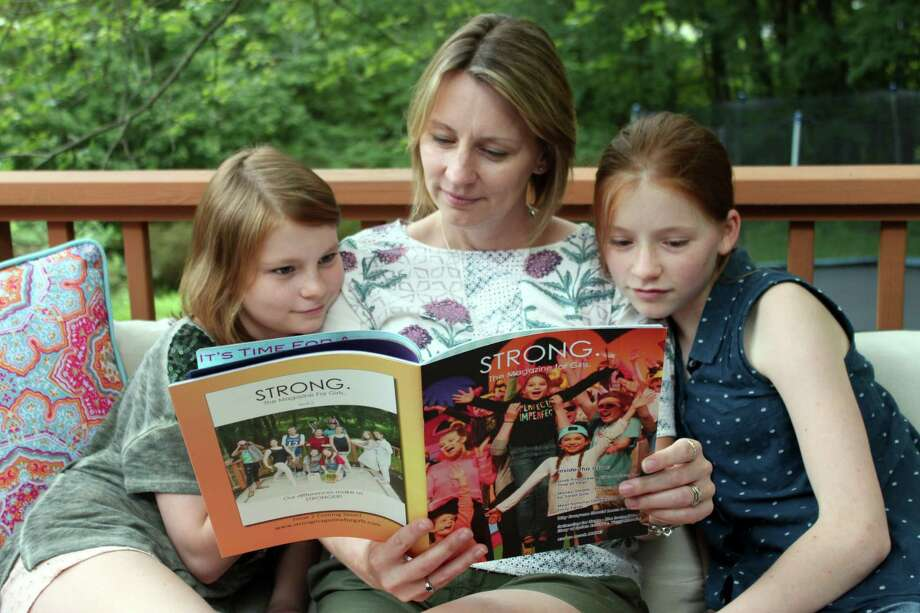"Sarah Beach and her daughters Daisy and Lucy look at the prototype of her magazine, ""STRONG."", at their home in Wilton. Photo: Stephanie Kim / Hearst Connecticut Media"