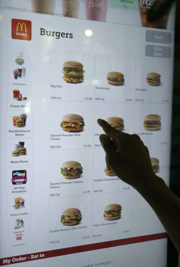 A customer orders food at a self-service kiosk at a McDonald's restaurant in Chicago. The company that helped define fast food is making supersized efforts to reverse its fading popularity and catch up to a landscape that has evolved around it. That includes expanding delivery, digital ordering kiosks in restaurants, and rolling out an app that saves precious seconds. Photo: Charles Rex Arbogast /Associated Press / Copyright 2017 The Associated Press. All rights reserved.