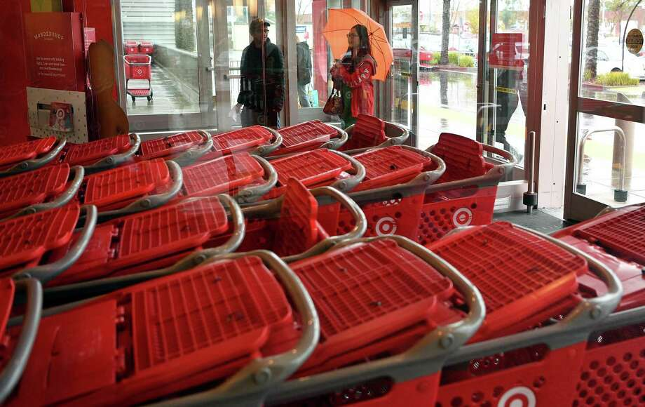 Shoppers enter a Target store during a rain storm in Emeryville, Calif. Target expects a modest increase in sales at existing stores, reversing four consecutive quarters of declines. Photo: San Francisco Chronicle File Photo / JOSH EDELSON / SPECIAL TO THE CHRONICLE