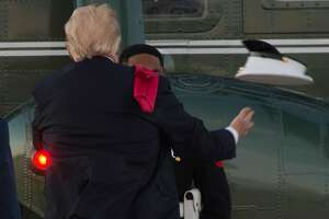 US President Donald Trump tries to catch a hat that the wind had blown from the head of a US Marine guarding Marine One following Trump's arrival at Andrews Air Force Base in Maryland, July 8, 2017, following a 4-day trip to Poland and Germany for the G20 Summit. / AFP PHOTO / SAUL LOEBSAUL LOEB/AFP/Getty Images