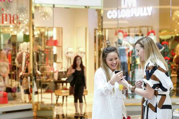 "Kristine Pagel, center, laughs with Haley Freytag, right, during an event to celebrate the opening of a remodeled luxury wing at the Galleria Thursday, July 13, 2017, in Houston. ""You get a lot of stores in one location, and the hands on feeling,"" Freytag said. ""It's that instant gratification.""  ( Jon Shapley  / Houston Chronicle )"