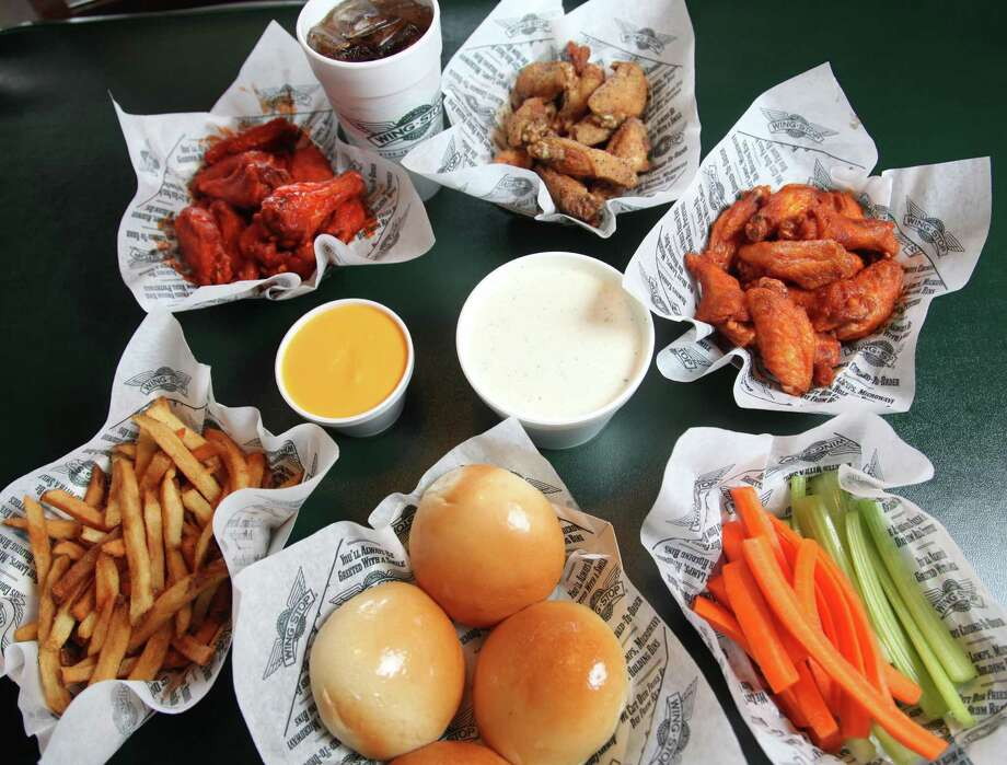 An assortment of wings from Wingstop include (from top left to right): original hot, lemon pepper and mild wings with cheese, ranch, fries, rolls, carrots and celery sticks. Photo: Staff File Photo / © 2012 San Antonio Express-News
