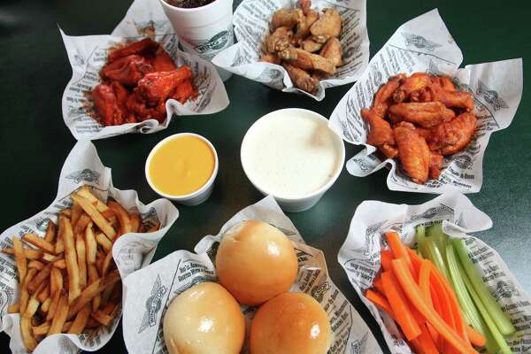 An assortment of wings from Wingstop include (from top left to right): original hot, lemon pepper and mild wings with cheese, ranch, fries, rolls, carrots and celery sticks.