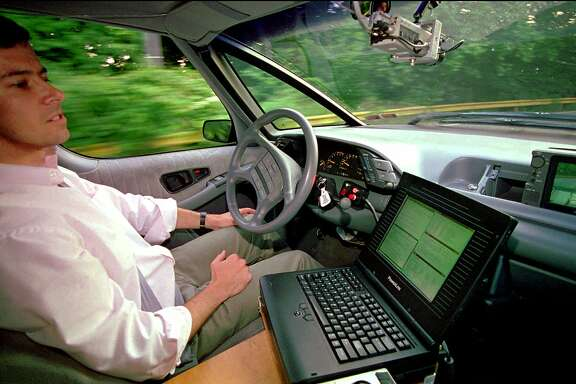 "FOR USE WITH FEATURE PACKAGE FOR JUNE 27--US SMART CARS--The landscape rushes by as Carnegie Mellon University Robotics Institute scientist Dean Pomerleau demonstrates ""hands free"" driving through Pittsburgh's Schenley Park near the school's campus on Monday, June 12, 1995. This computer controled vehicle uses a system that processes images from the video camera mounted near the rear-view mirror through the monitor at right to interface with the laptop computer at center. The system controls an electric motor to turn the steering column. The driver controls the speed and brakes. Pomerleau said he took the van from Pittsburgh to Washington D.C. about 220 miles (350Km) over the Memorial Day weekend with the vehicle doing 96% of the driving using cruise control in conjunction with the robotic steering system.(AP Photo/Keith B. Srakocic)"