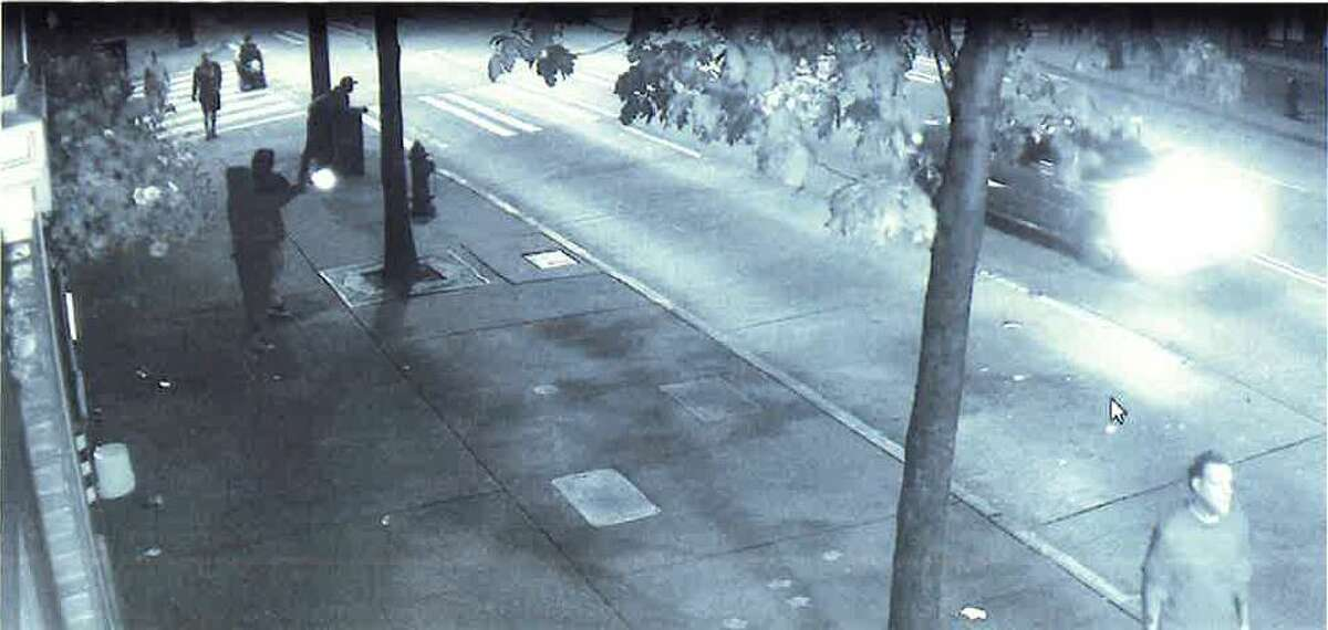 Surveillance footage showed two shooters firing at a passing Pontiac Grand Am the night of May 27. Two people in the car and a bystander on the sidewalk were injured in the incident.