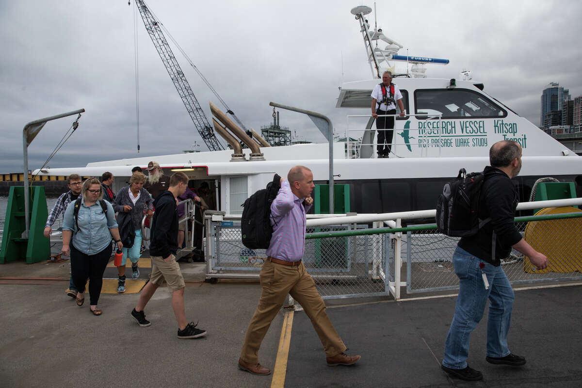 Morning commuters walk off Kitsap Transit's new fast ferry on Wednesday morning, July 13, 2017.