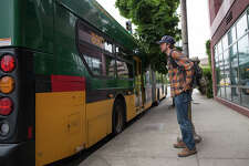 SeattlePI.com writer Daniel DeMay waits for his bus to pass after dropping him off new the Seattle P.I. globe on Wednesday, July 13, 2017.