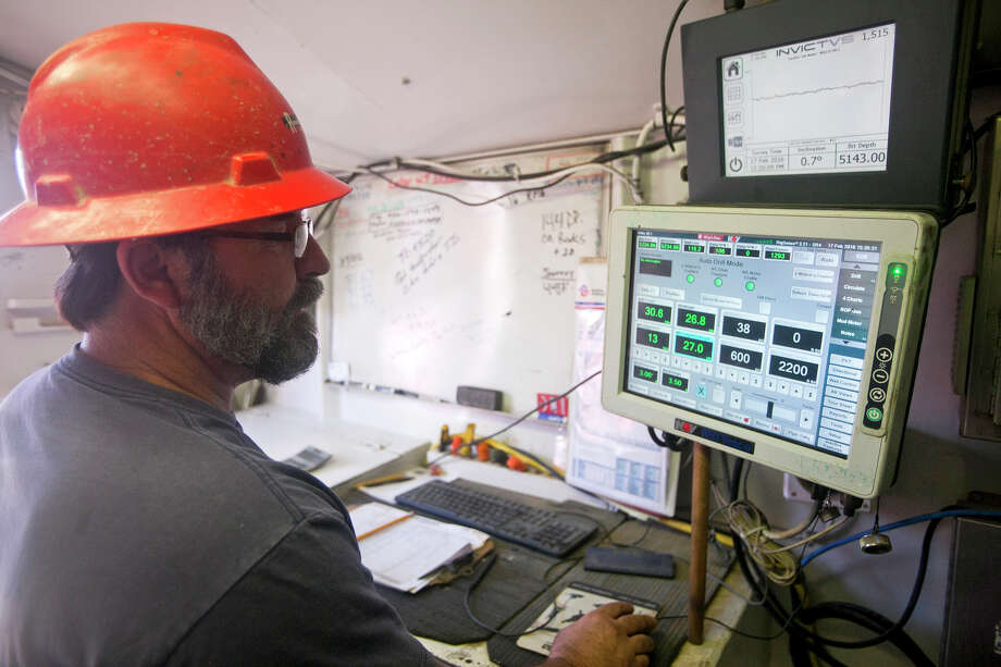 Jerry Moore, driller aboard Robinson Drilling rig #4, monitors activity from the control room on Wednesday, Feb. 17, 2016, in Midland County.  James Durbin/Reporter-Telegram Photo: James Durbin