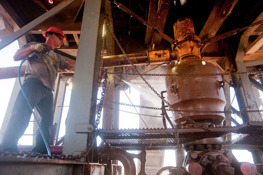 Carl Merworth washes the underside of Robinson Drilling rig #4 on Wednesday Feb. 17 2016 in Midland County. The drum-shaped item is the blowout preventer a large valve designed to seal the drill hole to prevent the uncontrolled release of oil or natu