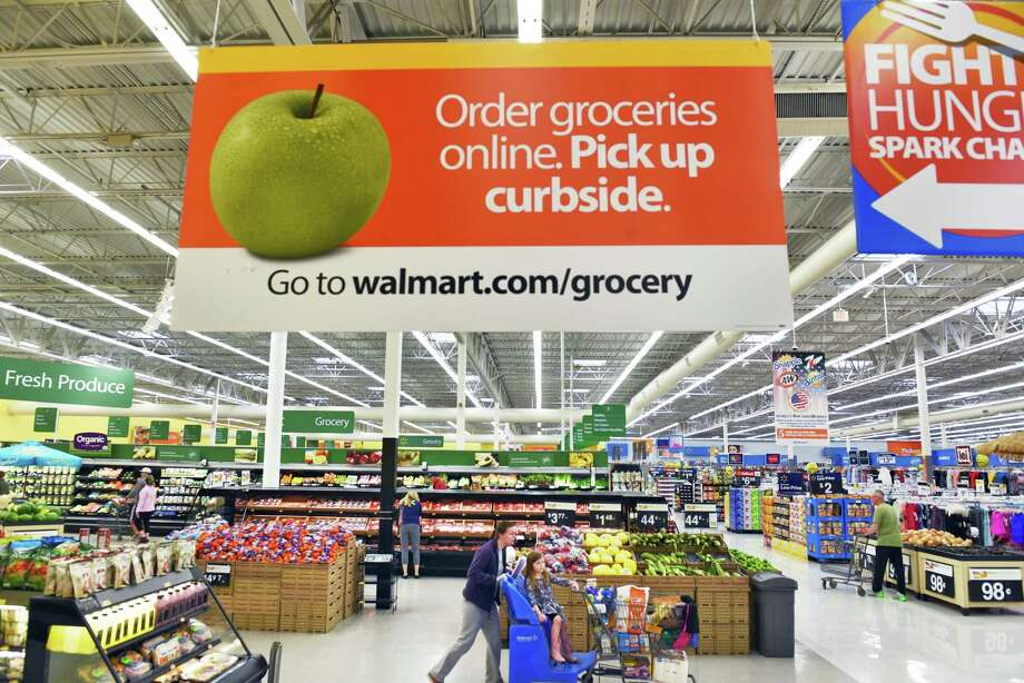 In-store signage announces the start of new online grocery pick up service at Walmart Stores in Halfmoon, N.Y. in May. The world's largest retailer is making hundreds of school staples like notebooks and pens available through its the online service. Photo: John Carl D'Annibale /Albany Times Union / 20040405A