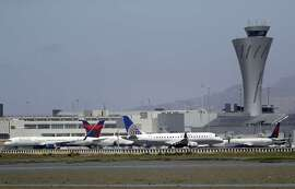 Departing and parked aircraft intersect at San Francisco International Airport, Tuesday, July 11, 2017, in San Francisco. An Air Canada Airbus A320 was cleared to land on one of the runways at SFO just before midnight on Friday, July 7, when the pilot was ordered to abort the landing after coming 100 feet from hitting planes waiting on a taxiway for takeoff.
