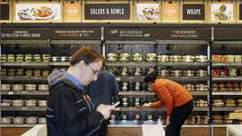 FILE - In this Thursday, April 27, 2017, file photo, shoppers roam through an Amazon Go store, currently open only to Amazon employees, in Seattle. Amazon Go shops are convenience stores that don't use cashiers or checkout lines, but use a tracking system that of sensors, algorithms, and cameras to determine what a customer has bought. Amazon�s nearly $14 billion deal for Whole Foods isn�t just about getting more than 460 grocery stores. Ultimately, Amazon wants to sell Amazon and Whole Foods shoppers alike even more goods and services, including stuff they might not even realize they need. (AP Photo/Elaine Thompson, File)